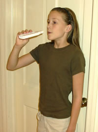 image of child holding peak flow meter before blowing out breath